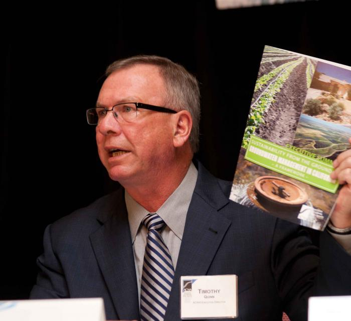 ACWA Executive Director Tim Quinn  with a report produced by Association of California Water Agencies on  sustainable groundwater management.